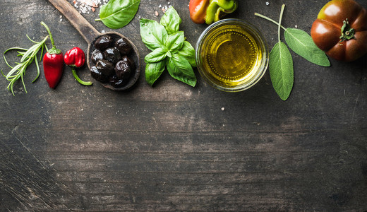 Food background with vegetables  herbs and condiment  Greek black olives  fresh basil  sage  rosemary  tomato  peppers  oil on dark rustic wooden background
