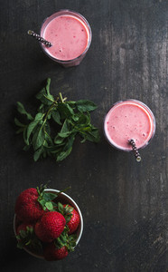 Strawberry and mint smoothie in tall glasses  bawl of fresh berries on dark rustic wood background