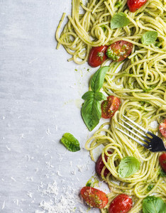 Spaghetti with pesto sauce  roasted cherry tomatoes  fresh basil and parmesan cheese on steel background