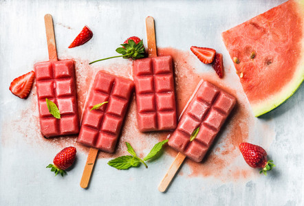 Strawberry watermelon ice cream popsicles with mint over steel tray background