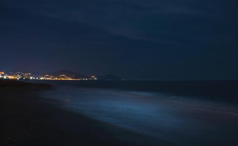Night scape of the sea coast  Beach in darkness  city lights at horizon  Alanya  Turkey