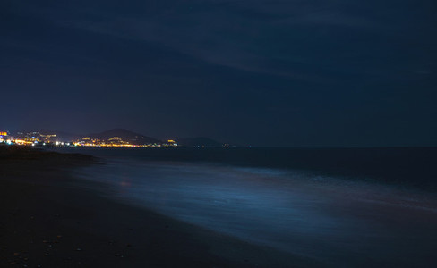 Night scape of the sea coast  Beach in darkness  city lights at horizon  Alanya  Turkey