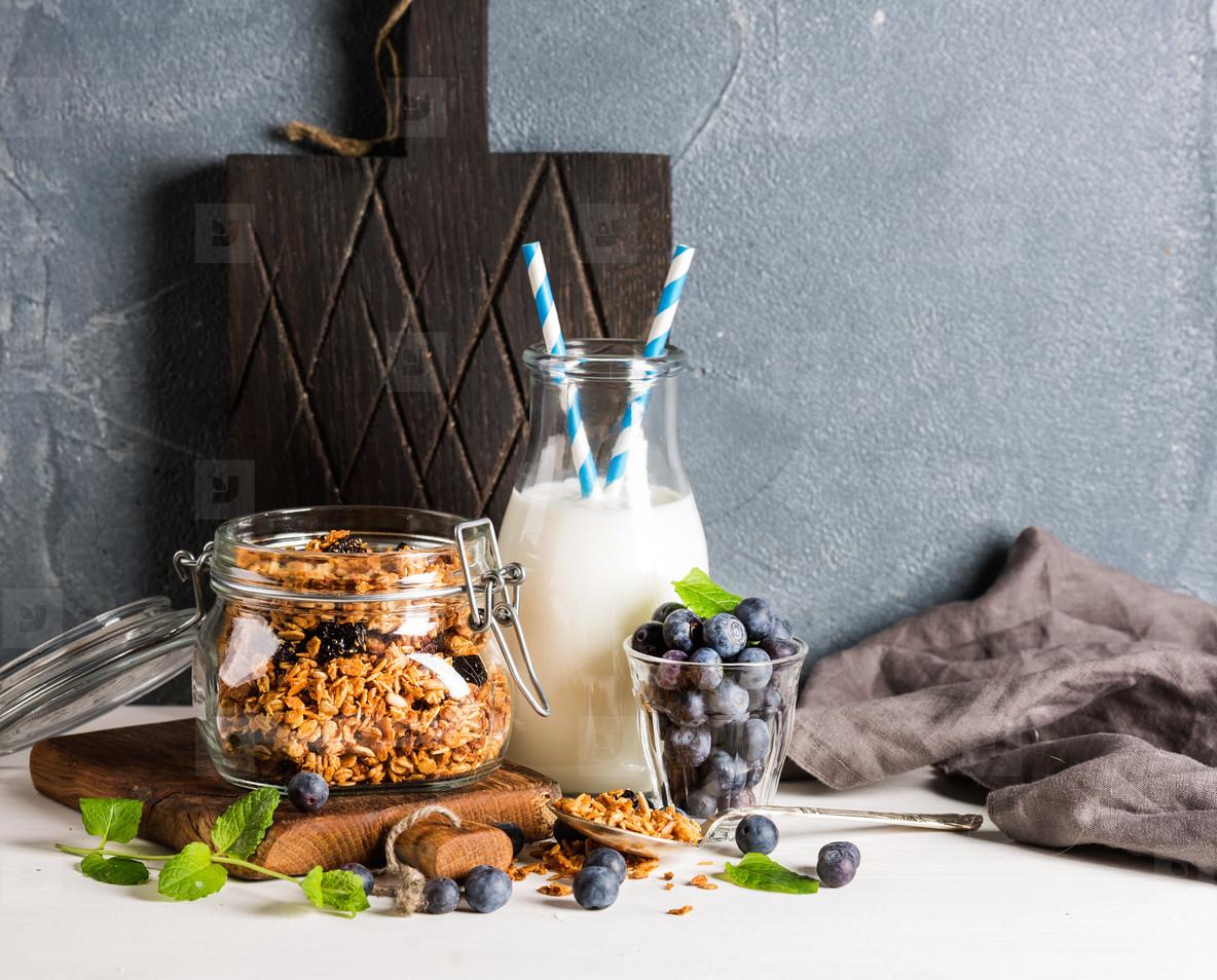 Healthy breakfast ingrediens  Homemade granola in open glass jar  milk or yogurt bottle  blueberries and mint
