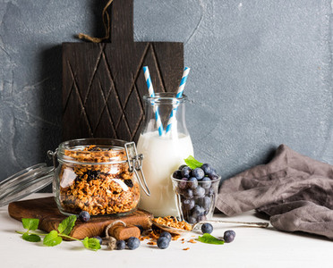 Healthy breakfast ingrediens  Homemade granola in open glass jar  milk or yogurt bottle  blueberries and mint