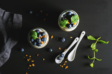 Healthy breakfast set  Yogurt oat granola with blueberries and mint leaves in glass jars on black backdrop