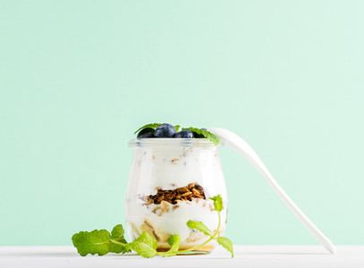 Yogurt oat granola with jam  blueberries and green leaves in glass jar on mint backdrop