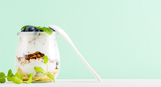 Yogurt oat granola with jam  blueberries and green leaves in glass jar on pastel mint backdrop
