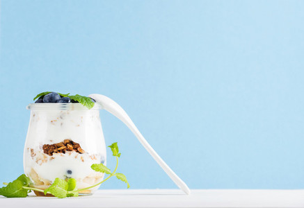 Yogurt oat granola with jam  blueberries and green leaves in glass jar on pastel blue backdrop