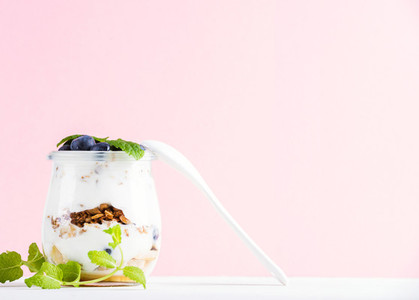 Yogurt oat granola with jam  blueberries and green leaves in glass jar on pink pastel backdrop