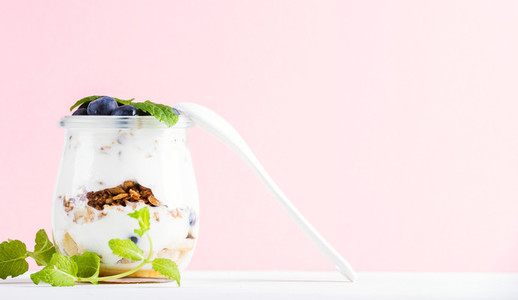 Yogurt oat granola with jam  blueberries and green leaves in glass jar on pastel pink backdrop