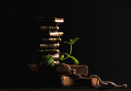 Triple layaered chocolate pieces stack or tower with banch of fresh mint on black background