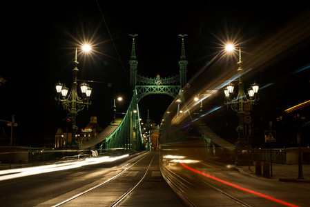 Night view of tram and cars crossing Liberty Bridge in Budapest  Hungary