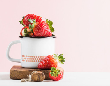 Fresh ripe red strawberries in country style enamel mug on rustic wooden board  pastel light pink background
