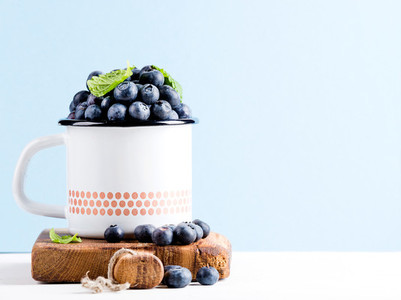 Fresh ripe blueberries in country style enamel mug on rustic wooden board over blue pastel background