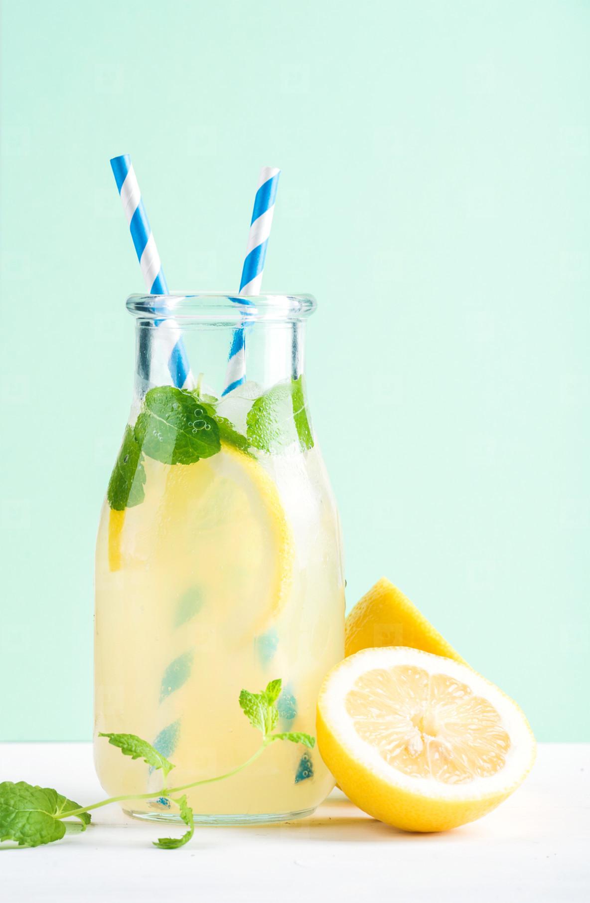 Bottle of homemade lemonade with mint  ice  lemons  paper straws and pastel blue background