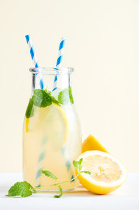 Bottle of homemade lemonade with mint ice lemons paper straws and pastel blue background