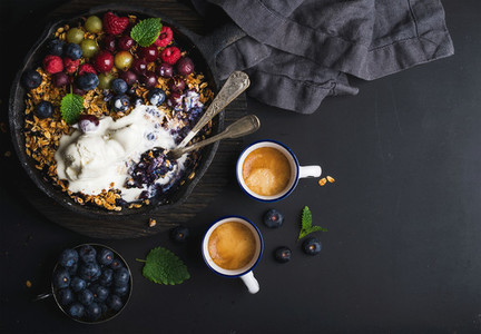 Healthy breakfast  Oat granola crumble with fresh berries  seeds and ice cream in iron skillet pan on dark wooden board  coffee over black backdrop  top view