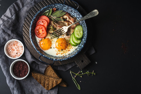 Breakfast set  Pan of fried eggs with bacon  fresh tomato  cucumber  sage and bread on dark serving board over black background