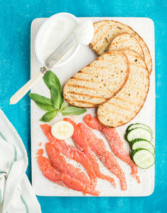 Ingredients for healthy sandwich  Grilled bread slices  smoked salmon  cottage cheese  cucumber and basil on white wooden board