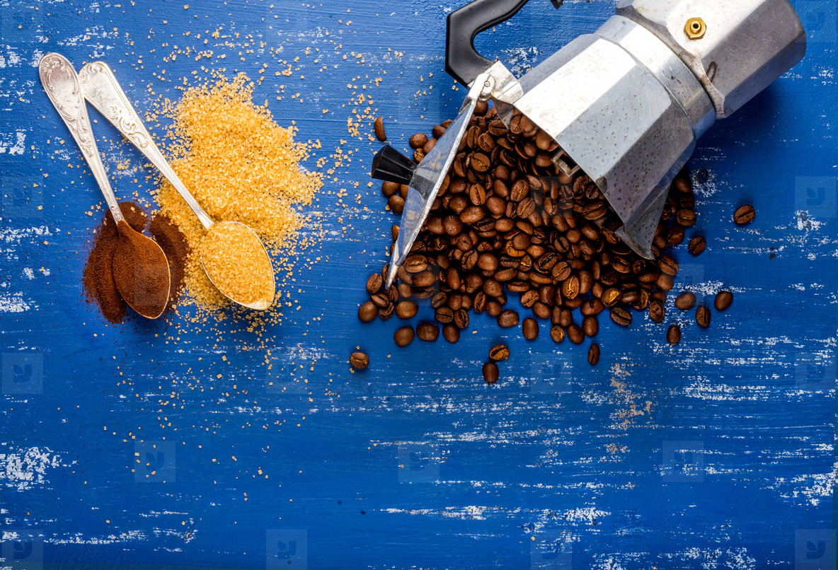 Arabika eans in moka pot brown sugar and ground coffee on wooden blue painted table