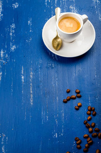 Cup of espresso coffee and beans on wooden blue painted table