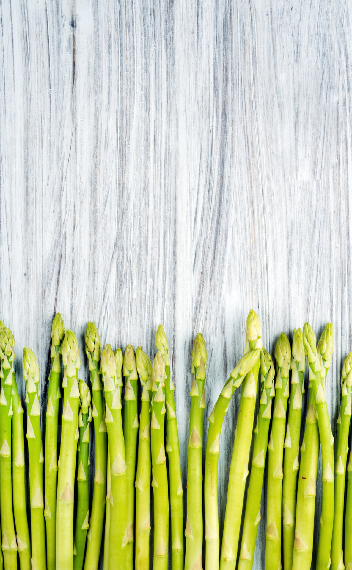 Green fresh sparagus on light painted wooden background