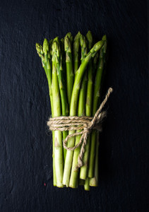 Green fresh asparagus on black slate stone background