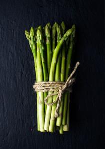 Green fresh asparagus on black slate stone background
