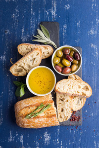 Mediterranean snacks set Olives oil herbs and sliced ciabatta bread on black slate stone board over painted dark blue background