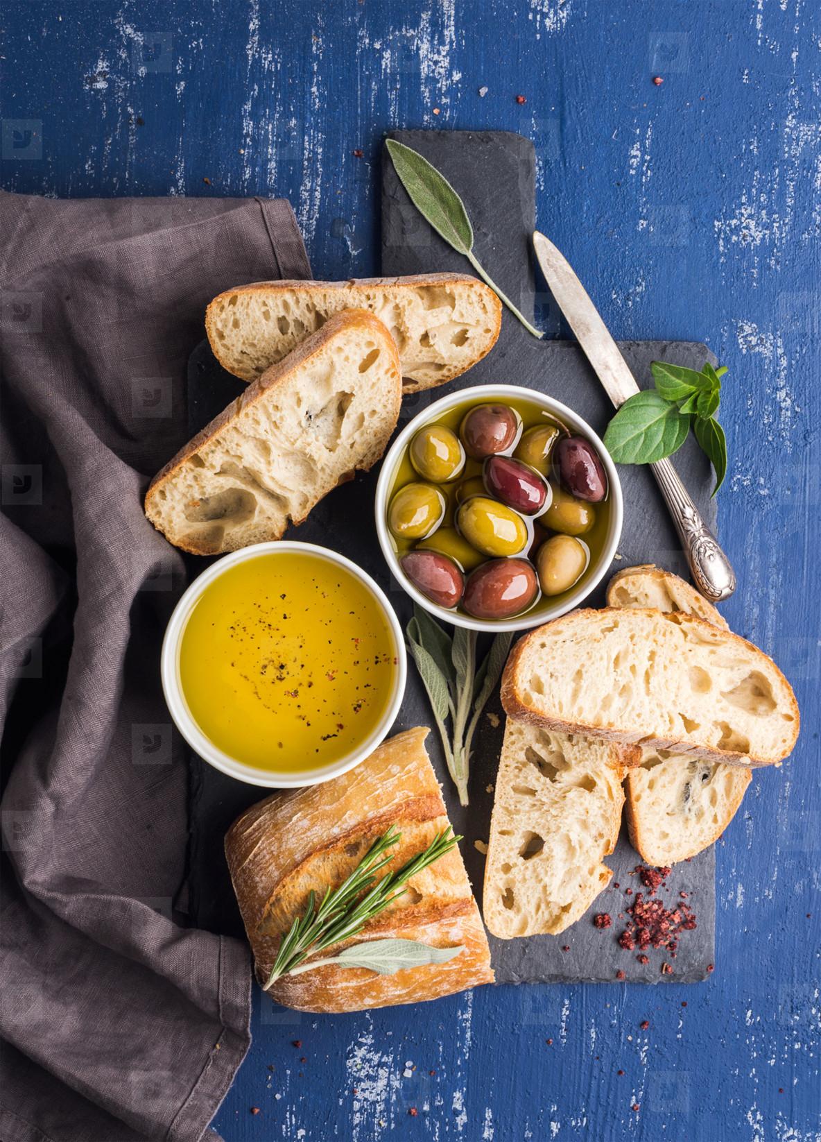 Mediterranean snacks set  Olives  oil  herbs and sliced ciabatta bread on black slate stone board over painted dark blue background