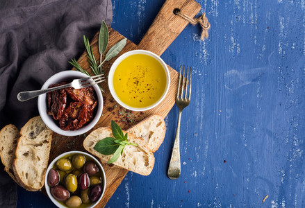 Mediterranean snacks set Olives oil herbs and sliced ciabatta bread on yellow rustic oak board over painted dark blue background