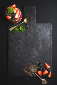 Healthy breakfast food frame Chia pudding with fresh berries and mint on black slate stone board over dark background