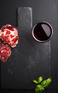 Glass of red wine  meat appetizer and basil on black  slate stone board over dark background