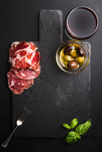 Glass of red wine meat appetizer olives and basil on black  slate stone board over dark background