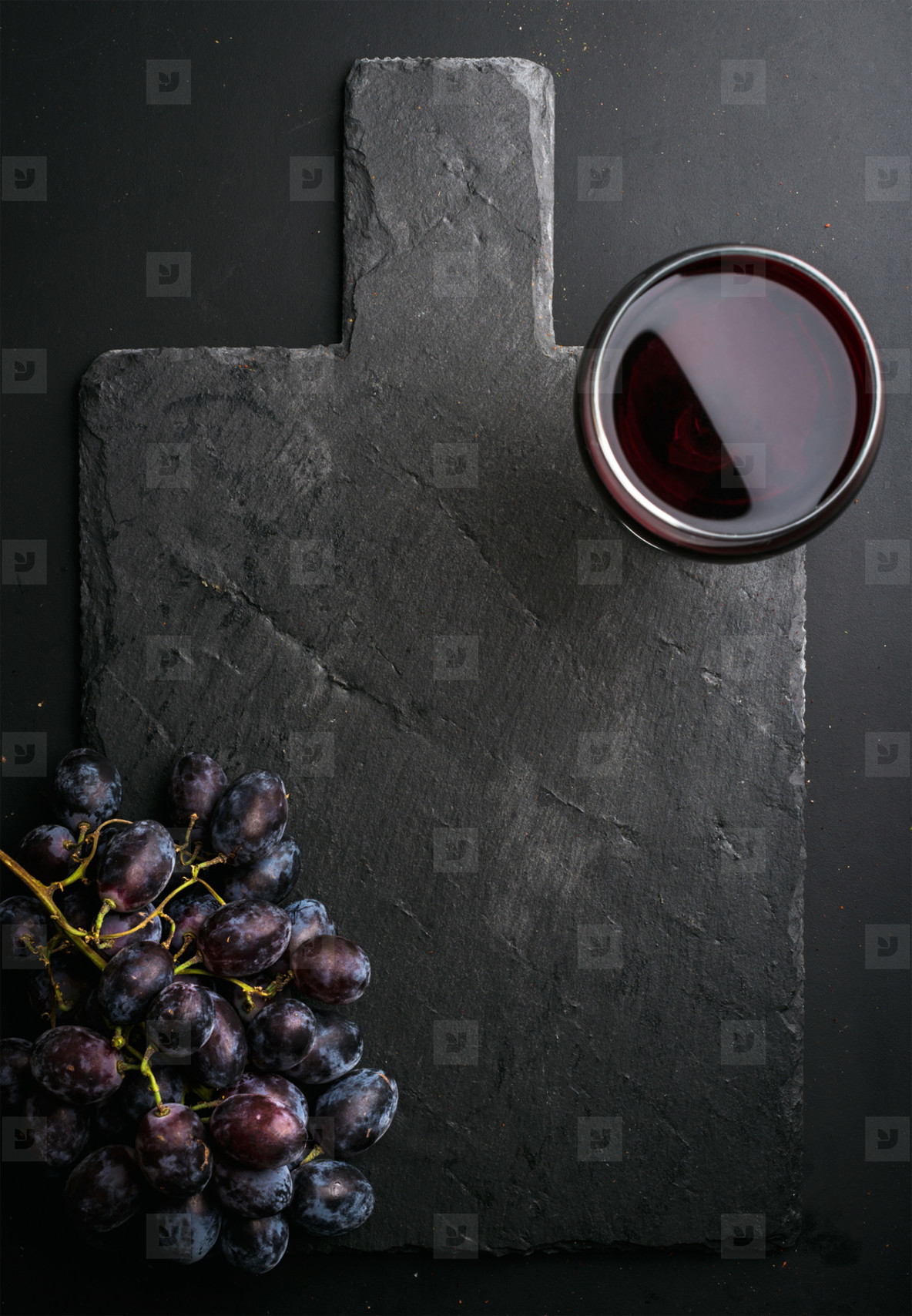 Glass of red wine and grapes on black slate stone board over dark background