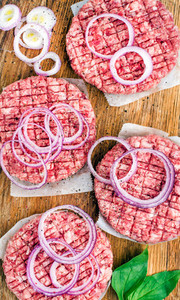 Raw ground beef meat cutlet for making burgers with onion rings and spices on wooden background
