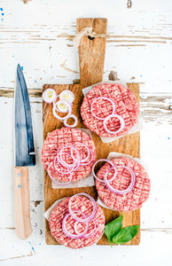 Raw ground beef meat cutlet for making burgers with onion rings and spices on wooden board over white backgroun