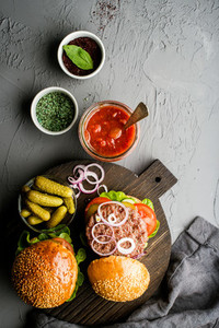 Fresh homemade burgers on dark serving board with spicy tomato sauce  green salt  pepper  pickles and onion over concrete textured background