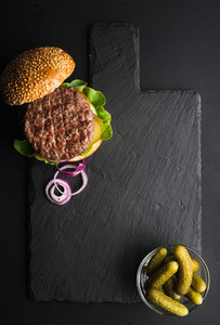 Fresh homemade burger on dark slate stone board  pickles and sliced onion over black background
