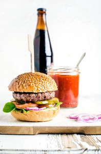 Fresh homemade burger on wooden serving board with spicy tomato sauce and bottle of dark beer white  background