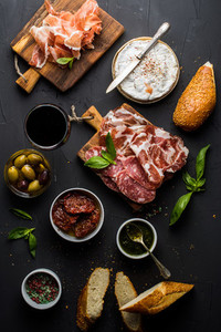 Wine snack set  Glass of red  meat selection  mediterranean olives  sun dried tomatoes  baguette slices  camembert cheese and spices on black background
