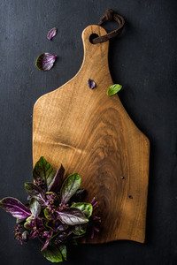 Violet basil bunch on wooden chopping board