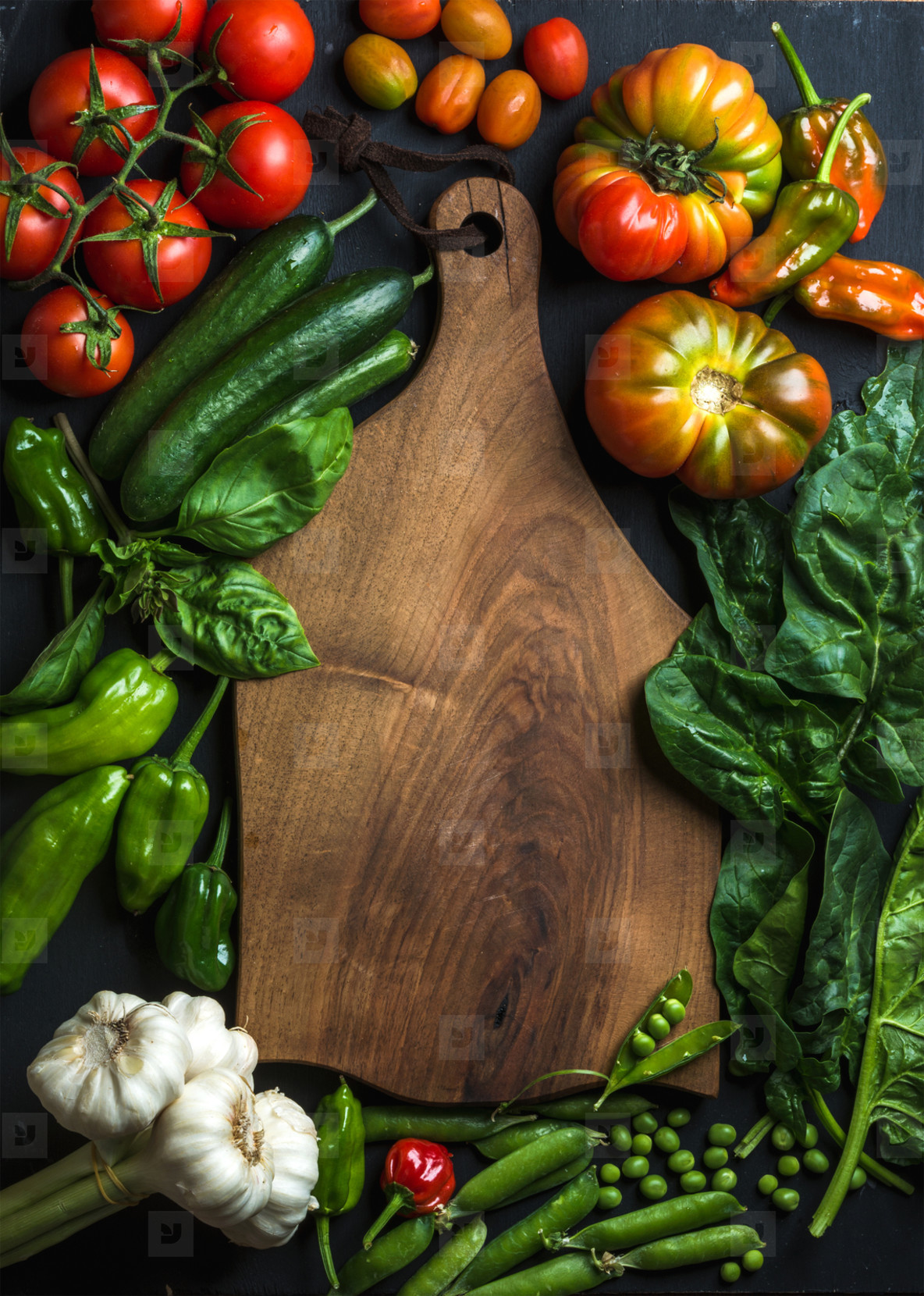 Fresh raw ingredients for healthy cooking or salad making with dark wooden cutting baoard in center  top view  copy space
