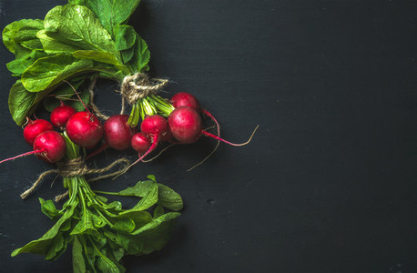 Bunch of radish with leaves on black background