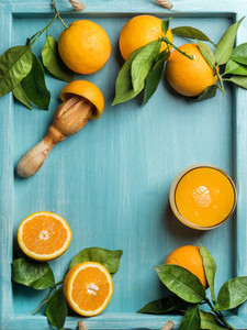 Fresh orange juice in glass and oranges with leaves on wooden turquoise blue painted background