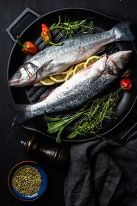Raw uncooked seabass fish with herbs and spices in cast iron cooking pan on black wooden background