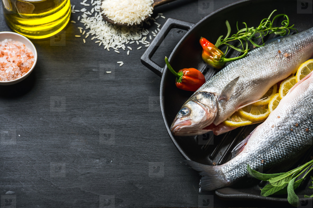 Raw uncooked seabass fish with herbs  spices and rice in cast iron cooking pan on black wooden background