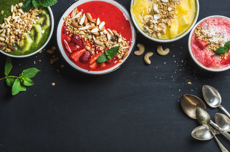Healthy summer breakfast concept  Colorful fruit smoothie bowls with nuts and oat granola on black background