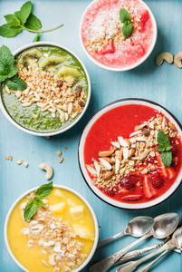 Healthy summer breakfast concept  Colorful fruit smoothie bowls on turquoise blue background