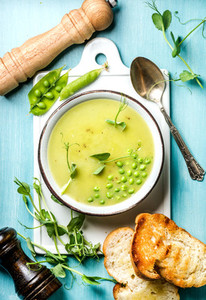Light summer green pea cream soup in bowl with sprouts  bread toasts and spices